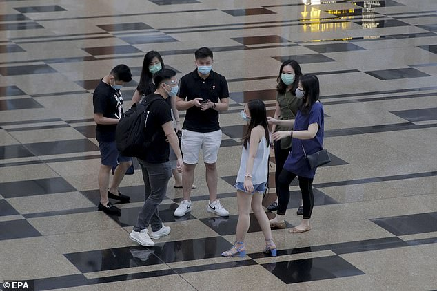 Singapore has reported more than 53,000 coronavirus infections, mostly due to mass outbreaks in cramped migrant workers dormitories. Above, a group of passengers stand in the departure hall of Changi Airport on July 30