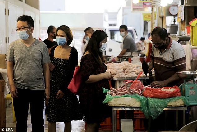 A couple walk past butcher stalls at the Tekka Market in Singapore on July 21. Singapore is expected to face its worst recession since gaining independence amid the Covid-19 pandemic
