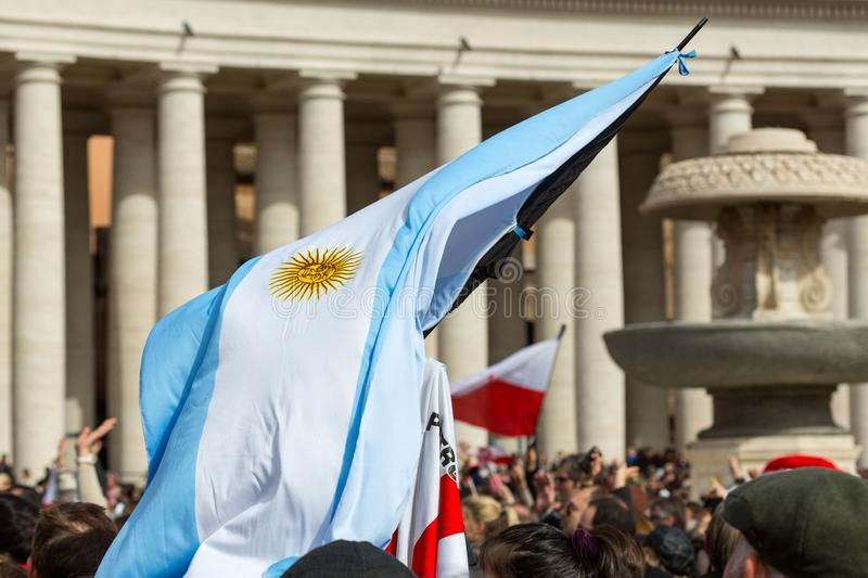An Argentinian Flag in St, Peter`s Square. Vatican City, Vatican - February 22, 2015: A crowd gathers in St. Peter`s Square while someone waves a Argentinian royalty free stock photography