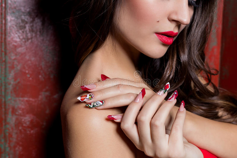 Beautiful well-groomed hands of a young girl with long fake acrylic nails with a festive Christmas pattern on the nails royalty free stock photo