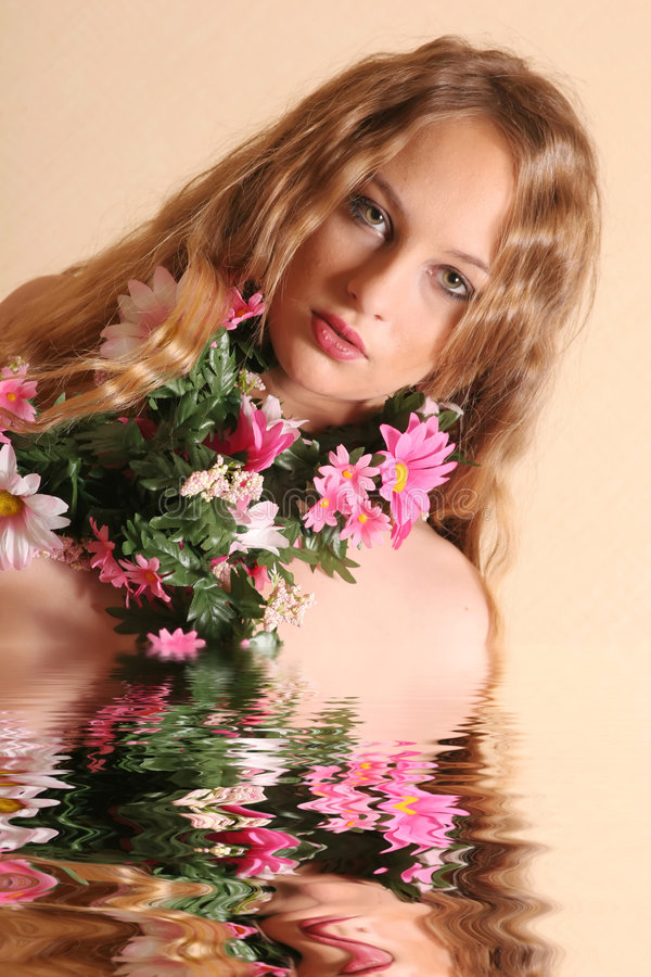 Beautiful woman in water. Young blond woman with flowers royalty free stock images