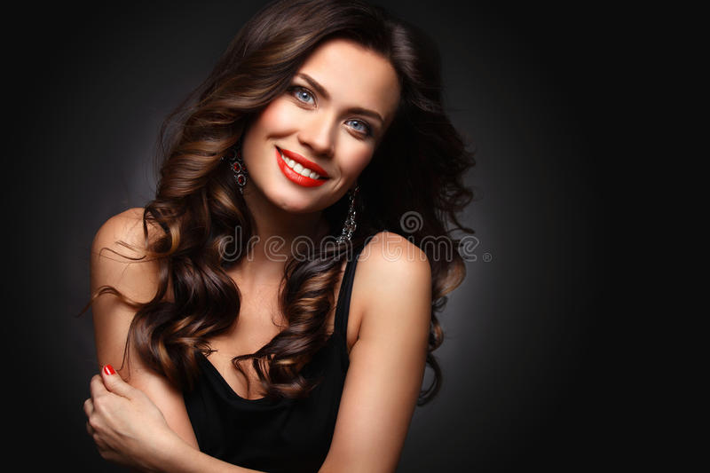 Beauty Model Woman with Long Brown Wavy Hair. Healthy Hair and Beautiful Professional Makeup. Red Lips and Smoky Eyes royalty free stock photo