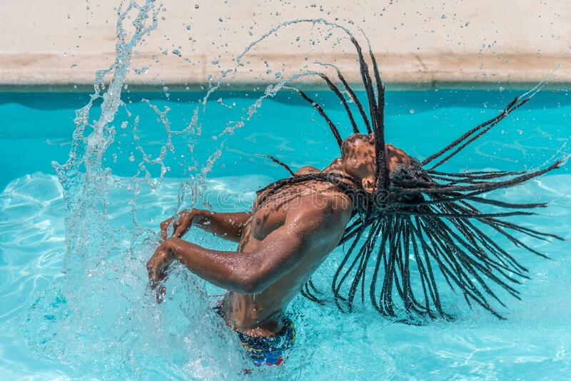 Black man with dreadlocks inside a pool raising his wet hair making a trail of water. High quality photo royalty free stock image
