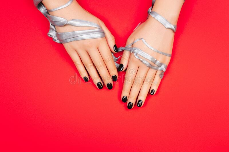 Black manicure on creative red background stock photo
