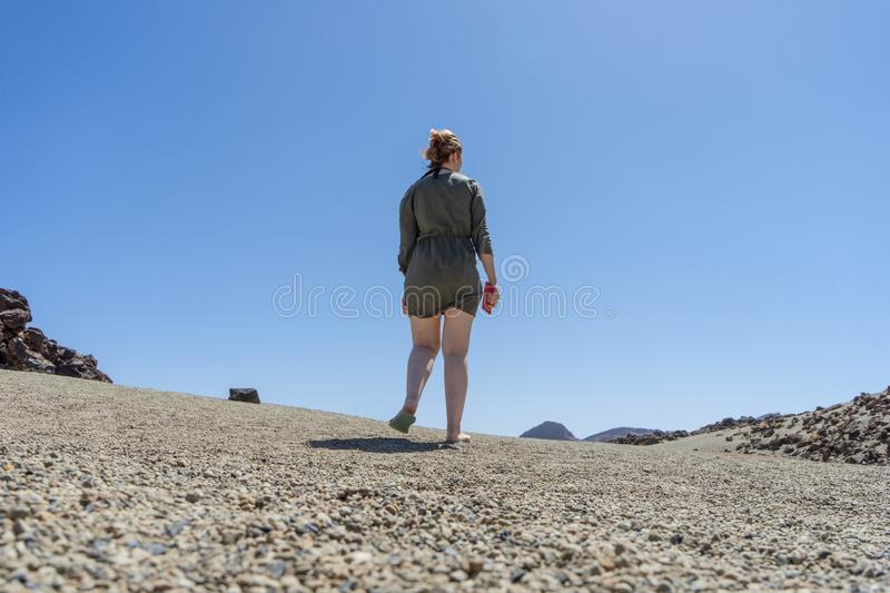 Blond hair teen in relaxing mood at remote lunar, volcanic and arid desert. Back of Spiritual woman in green dress walking alone. On volcano path with white stock photo