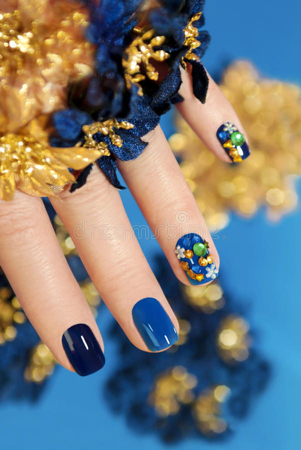 Blue and gold manicure. royalty free stock images