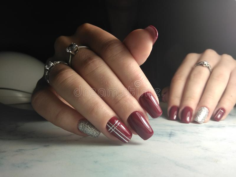 Bright Burgundy manicure with silver design. stock photography