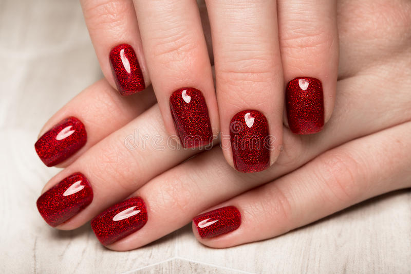 Bright festive red manicure on female hands. Nails design royalty free stock images