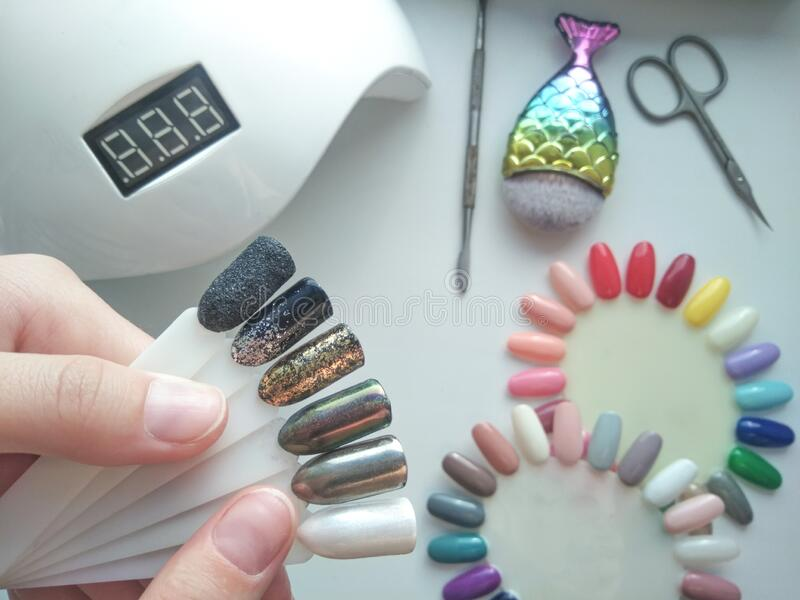 Bright shiny designs on the tips. Color palette. Drawings on nail tips with silver, gold and shiny coating stock photo