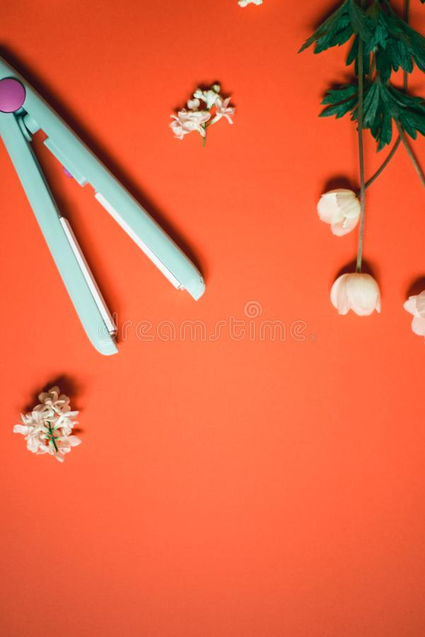 Curling iron ripple on a coral background. Hair accessory on orange background with flowers. Hairstyle tool.  stock image