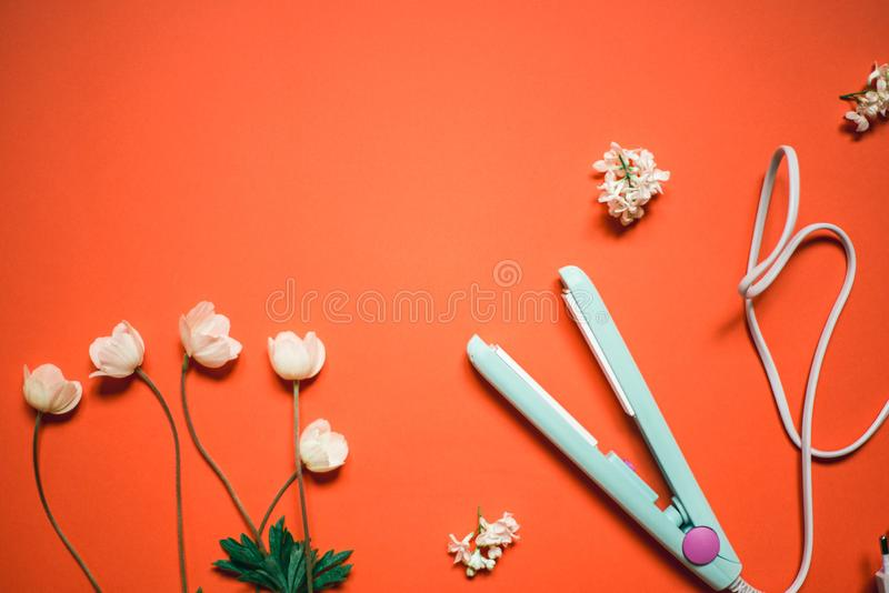 Curling iron ripple on a coral background. Hair accessory on orange background with flowers. Hairstyle tool.  royalty free stock photos