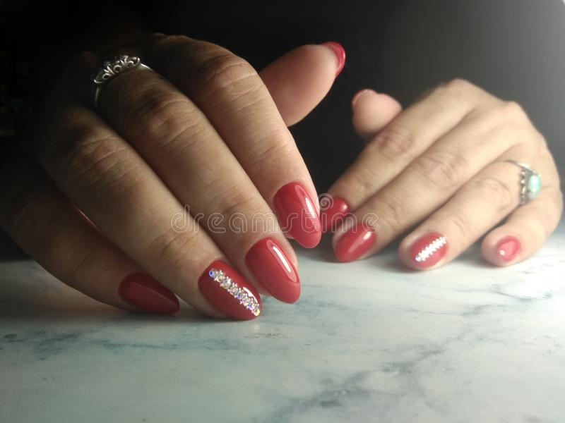 Cute manicure with red coating and rhinestones. royalty free stock photos
