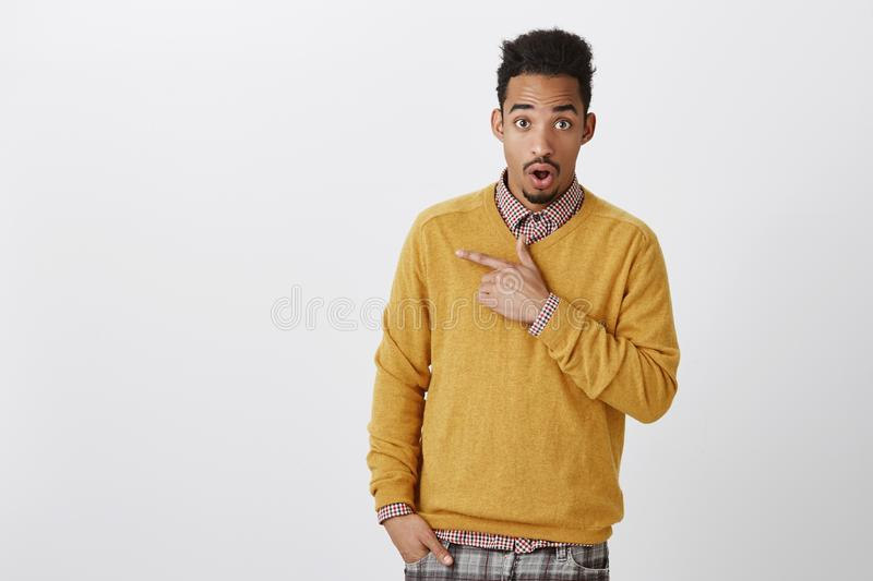Discussing with friend shocking gossip about classmate. Attractive african-american male student with afro hairstyle in. Yellow pullover, dropping jaw from stock photography