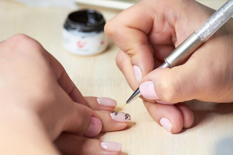 The drawing process on female nails. stock image
