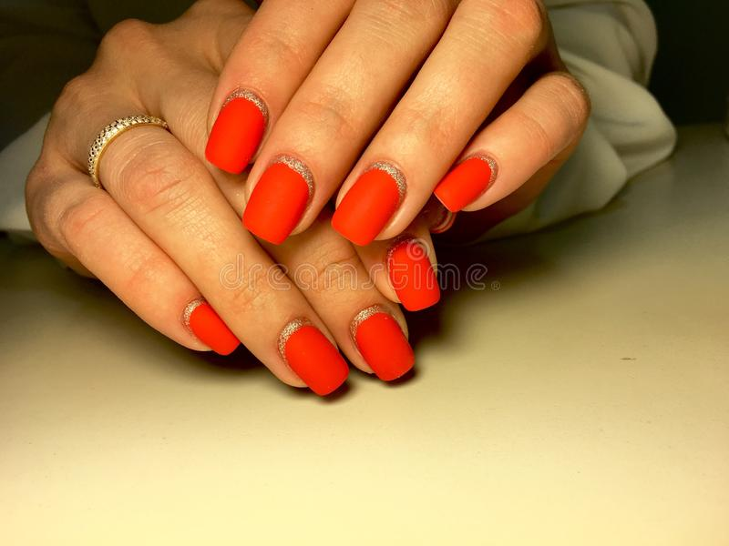 Fashionable red matte manicure on a textural background with silver royalty free stock photos