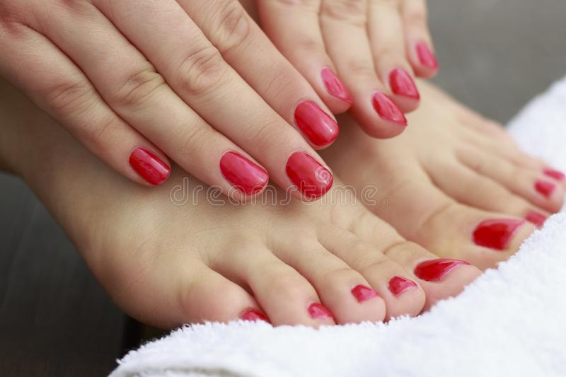 Female hands and feet with a red manicure and pedicure on wooden background royalty free stock photos