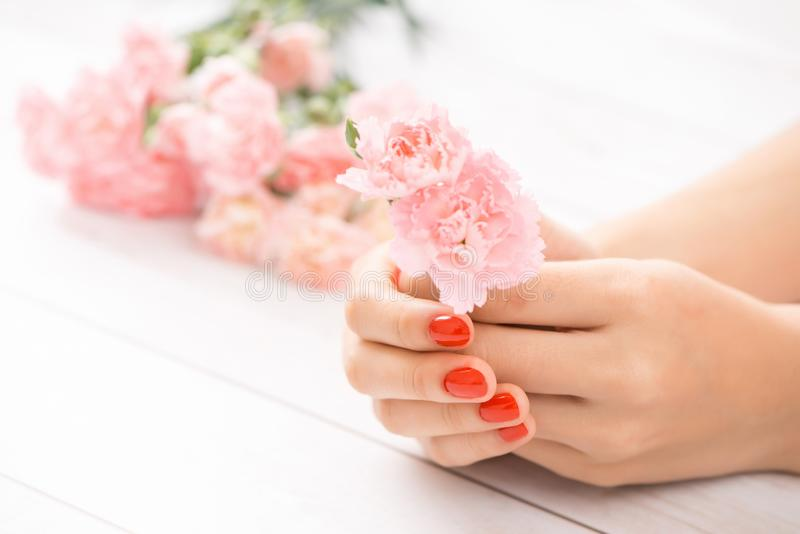 Female hands with red manicure and an open bottle of varnish on stock photo