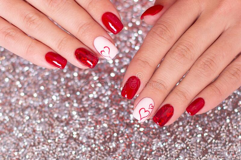 Female hands with romantic manicure, red gel polish, hearts on nails stock photos