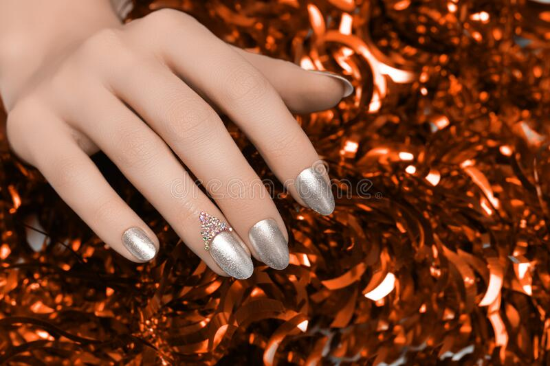 Female hands with silver Christmas nail design. Silver nail polish manicured hands. Female holding red New Year tinsel royalty free stock photos