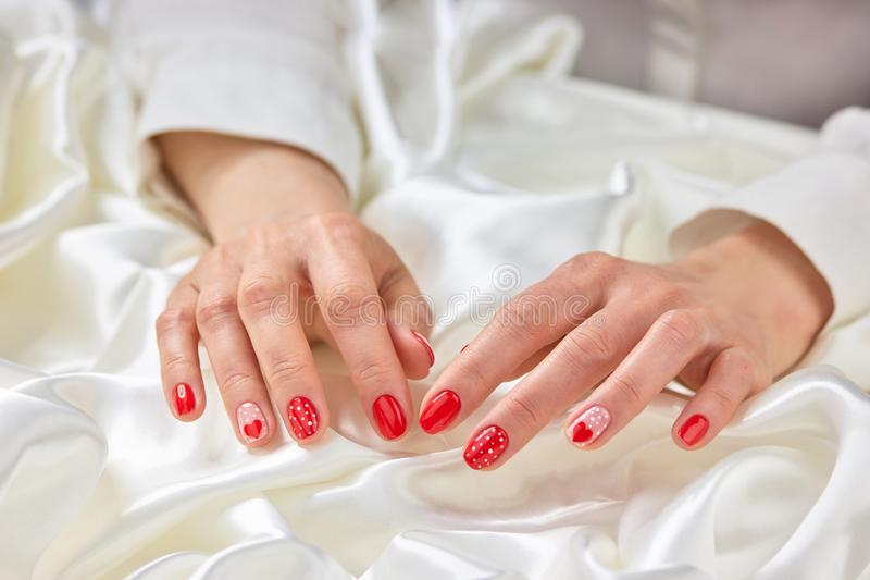 Female red manicure and white silk. stock photos