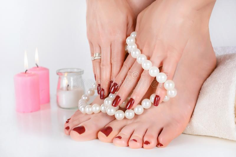 Girl feet and hands with dark red color manicure and pedicure stock photography
