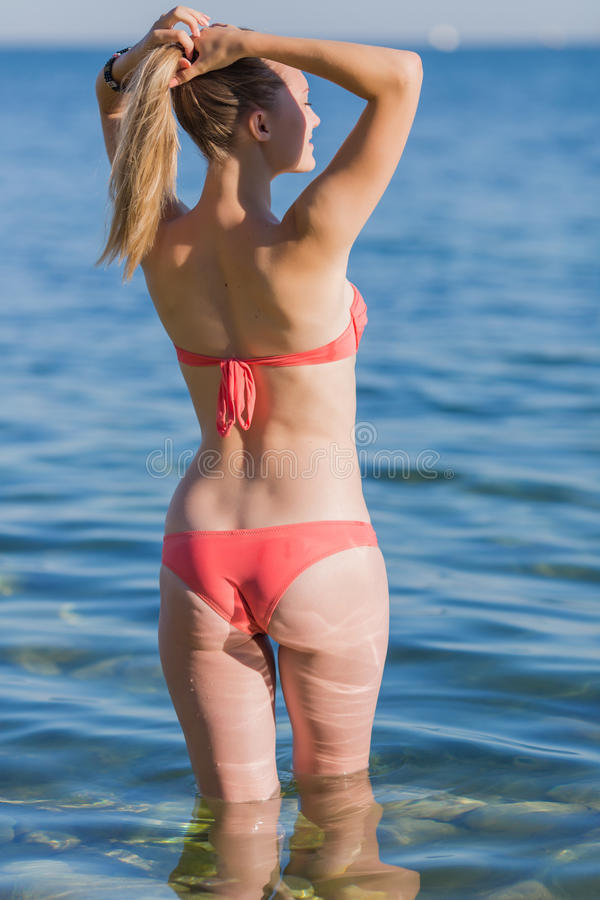 Girl at the sea. Young woman in pink bikini adjusts her hairstyle, rear view stock photo