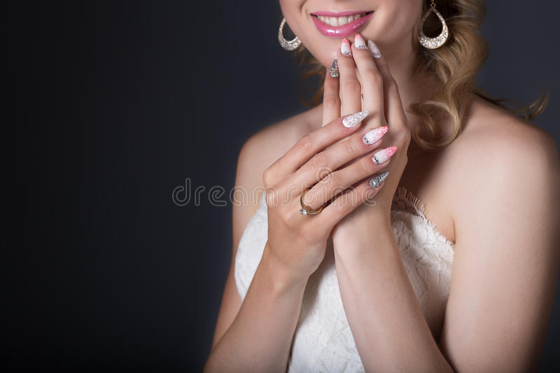 Hand beautiful girl bride in white wedding dress with acrylic nails and delicate pattern and rhinestones royalty free stock photography