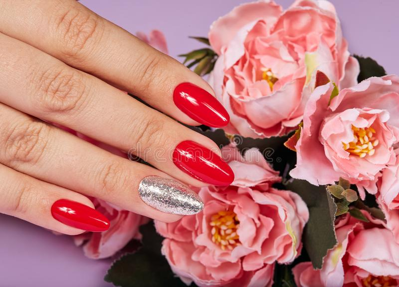 Hands with beautiful artificial manicured nails colored with red and silver nail polish stock image