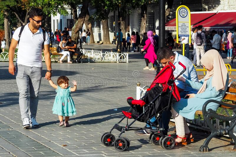 Man walks with a little girl, a daughter who waves her hand to a married couple sitting on a bench in Sultanahmet square. ISTANBUL, TURKEY - AUGUST 21, 2018: a stock photography