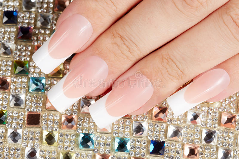 Nails with long artificial french manicure on colorful crystals background stock photo