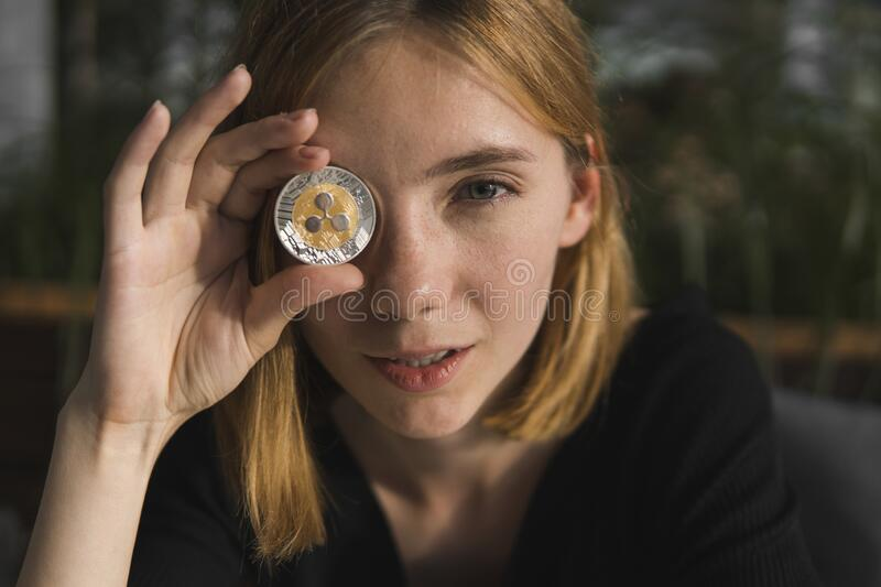 A nice girl is attaching a gold ripple coin to her eye. Bitcoins, crypto currency, electronic money. Woman sitting in. Cafe holding bitcoin in front eye stock image