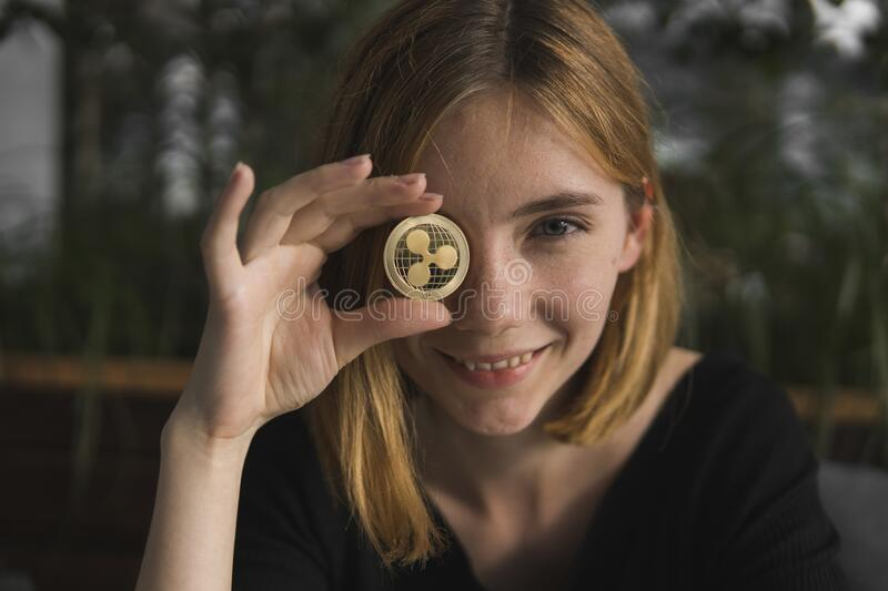 A nice girl is attaching a gold ripple coin to her eye. Bitcoins, crypto currency, electronic money. Woman sitting in. Cafe holding bitcoin in front eye royalty free stock photo