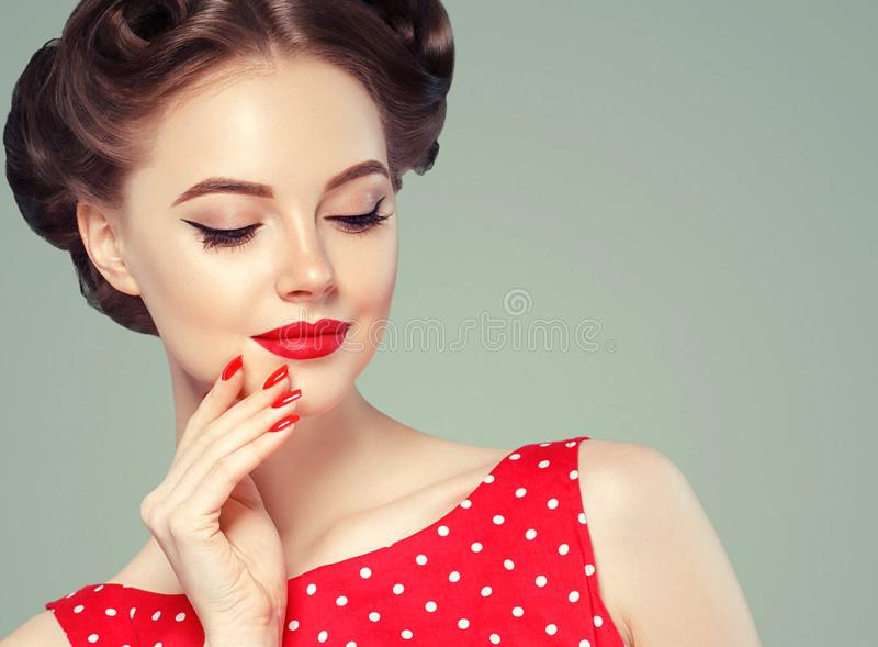 Pin up girl vintage. Beautiful woman pinup style portrait in retro dress and makeup, manicure nails hands, red lipstick and polka royalty free stock image