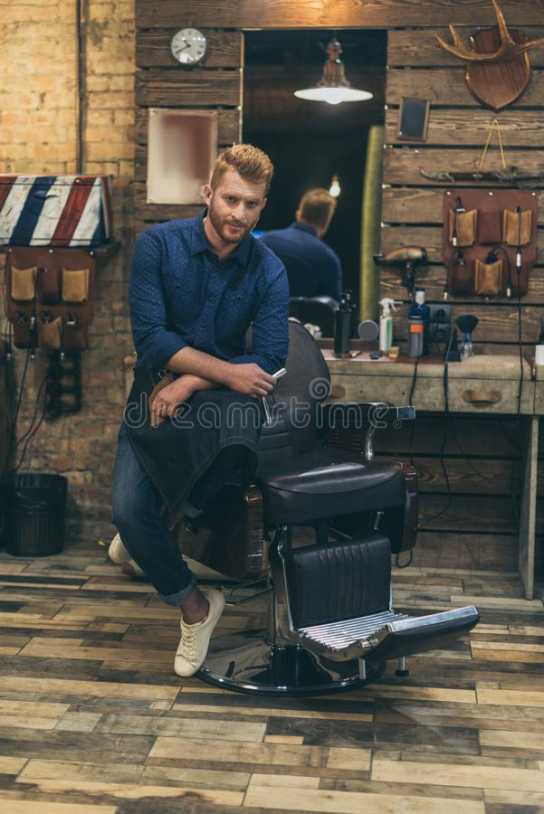 Portrait of handsome caucasian male barber with fashionable hairstyle. At barber shop stock photo