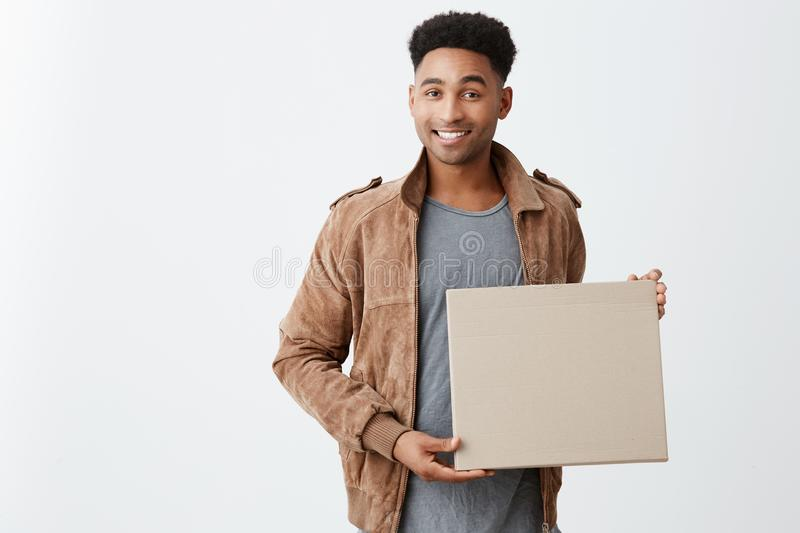 Positive emotions. Close up of young beautiful black-skinned male with afro hairstyle in casual stylish clothes holding. Cardboard in hands, looking in camera stock photos