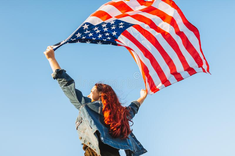 Red hair young woman standing facing the sky with her hands holding usa flag for freedom concept. 4th of July, Independence day.  stock photos