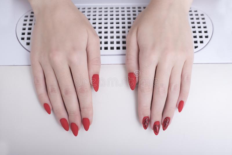 Red manicure with a pattern. Female hands in manicure salon royalty free stock images