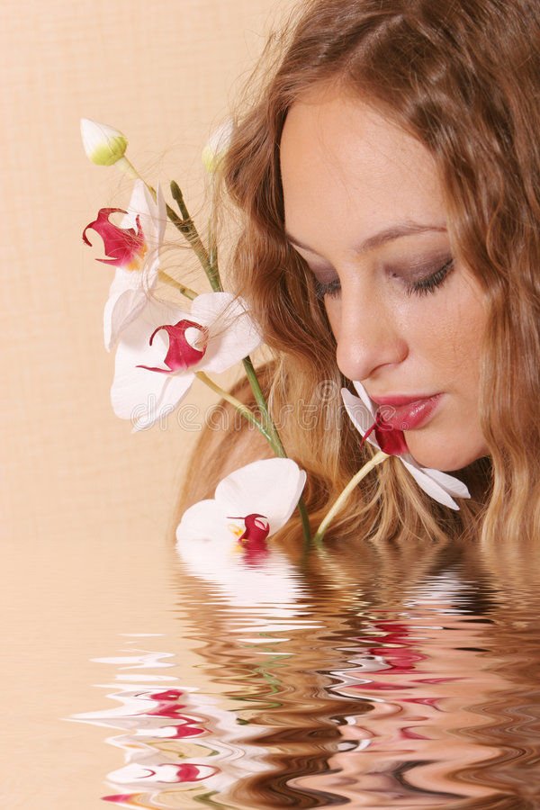 Young blond woman. With orchid royalty free stock photography