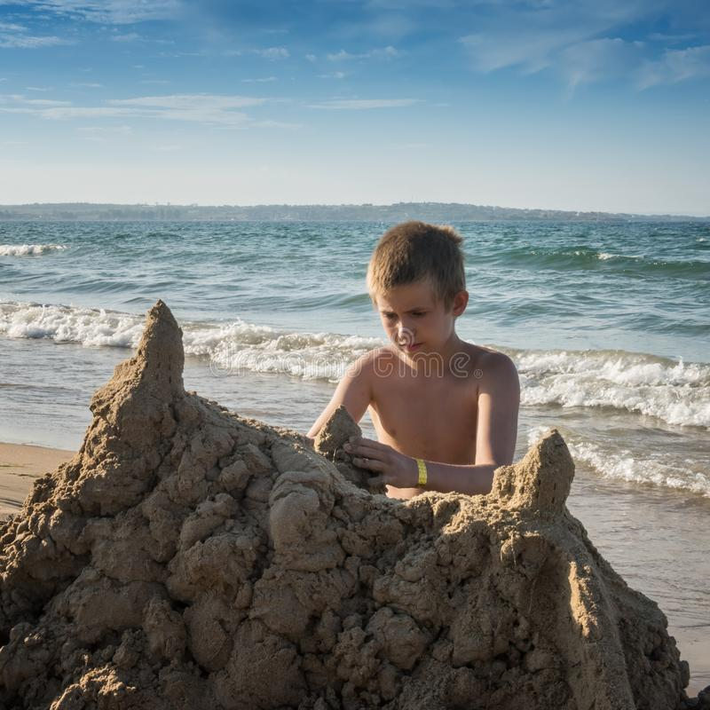 Square image of teenager with big sand castle. Square image of concentrated boy with yellow sand castle at the beach. Sea waves and blue sky with white clouds at stock image