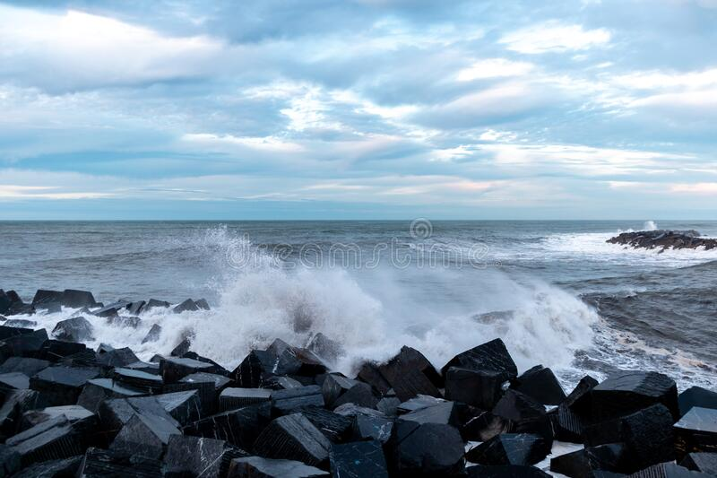 Waves breaking on the square rocks of the breakwater in Donostia, San Sebastian, Spain. Waves breaking on the square rocks of the breakwater in Donostia, San stock image