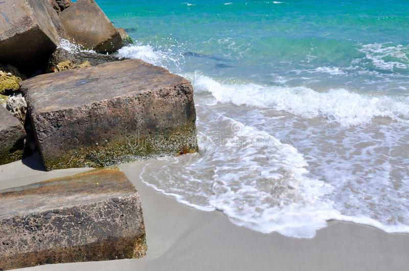 Waves Splashing Ecology Blocks: Breakwater in Australia. Square concrete ecology blocks in closeup with the turquoise Indian Ocean waters and gentle waves royalty free stock photo