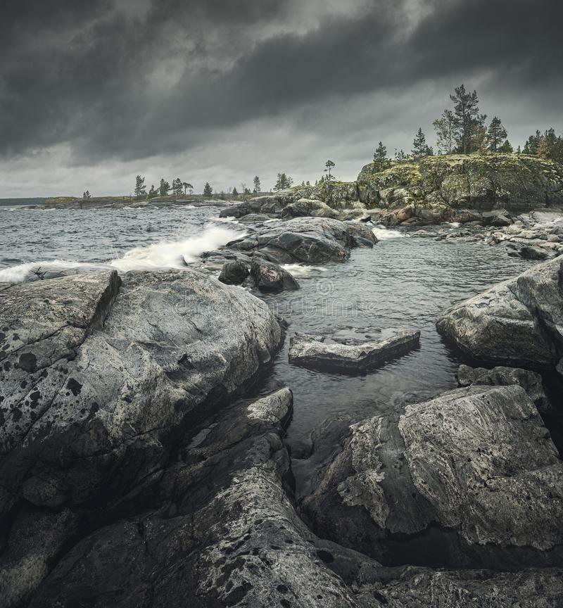 Waves of stormy sea break on rocky shore. Square layout for travel stories stock image