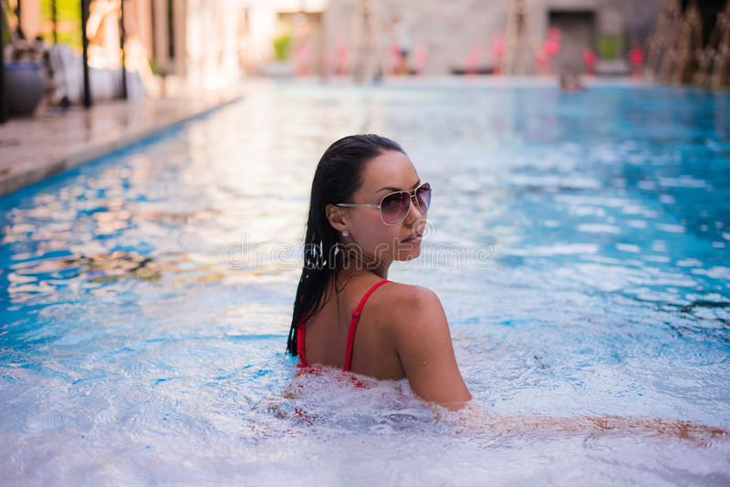 Woman with black hair lying back on the bassin rim of a swimming pool with rippled cool deep blue water.  royalty free stock photo