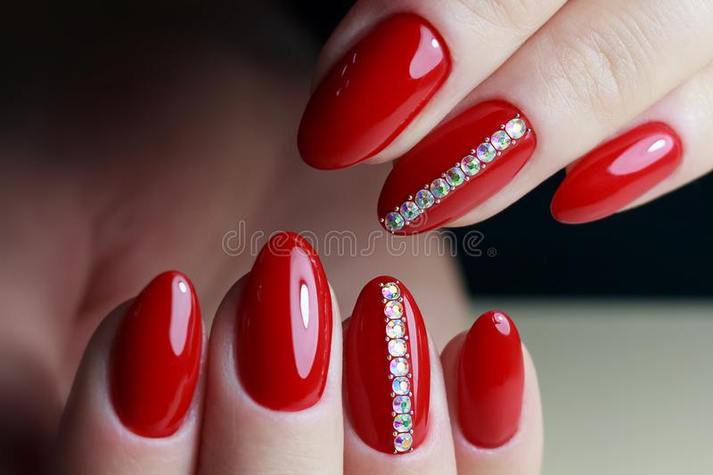 Woman hands with manicure nail polish on red background royalty free stock image