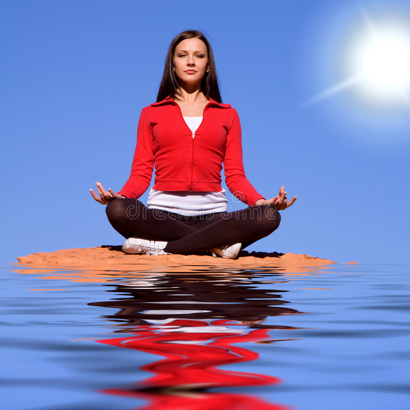 Woman meditating. Young woman meditating on red rocks stock photo