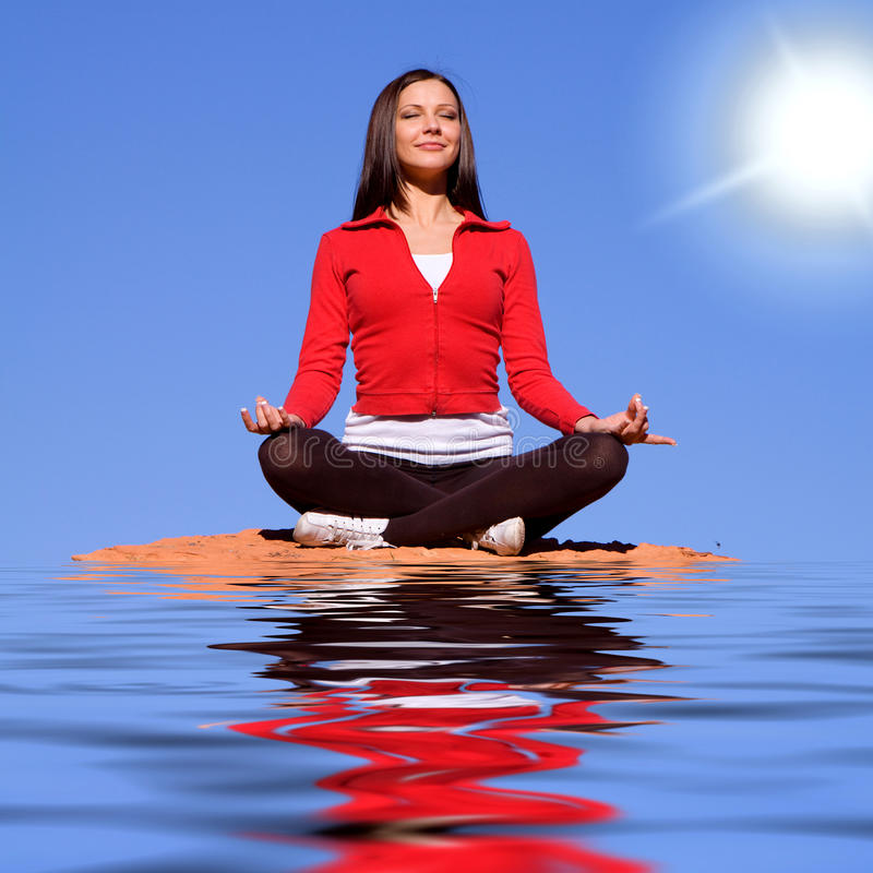 Woman meditating on rocks. Young woman meditating on red rocks stock images