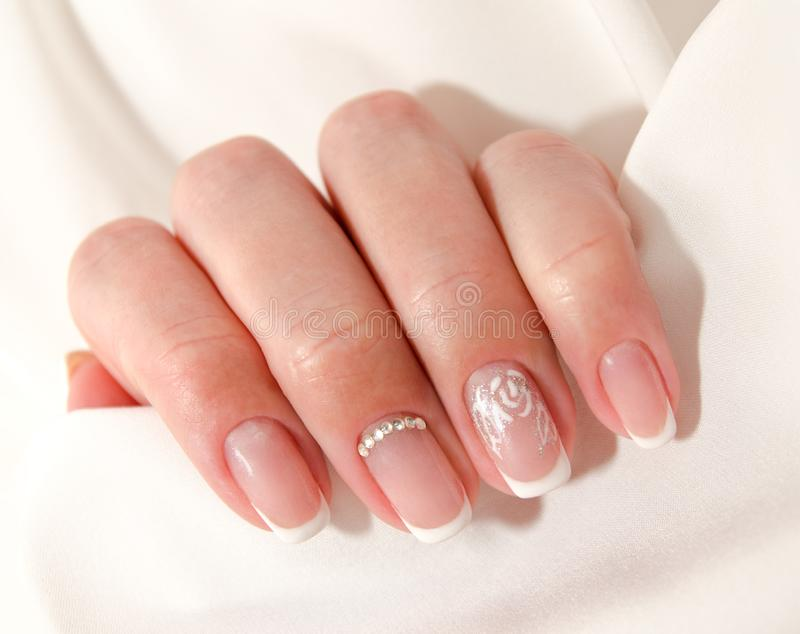 Woman`s nails with beautiful french manicure fashion design stock photography