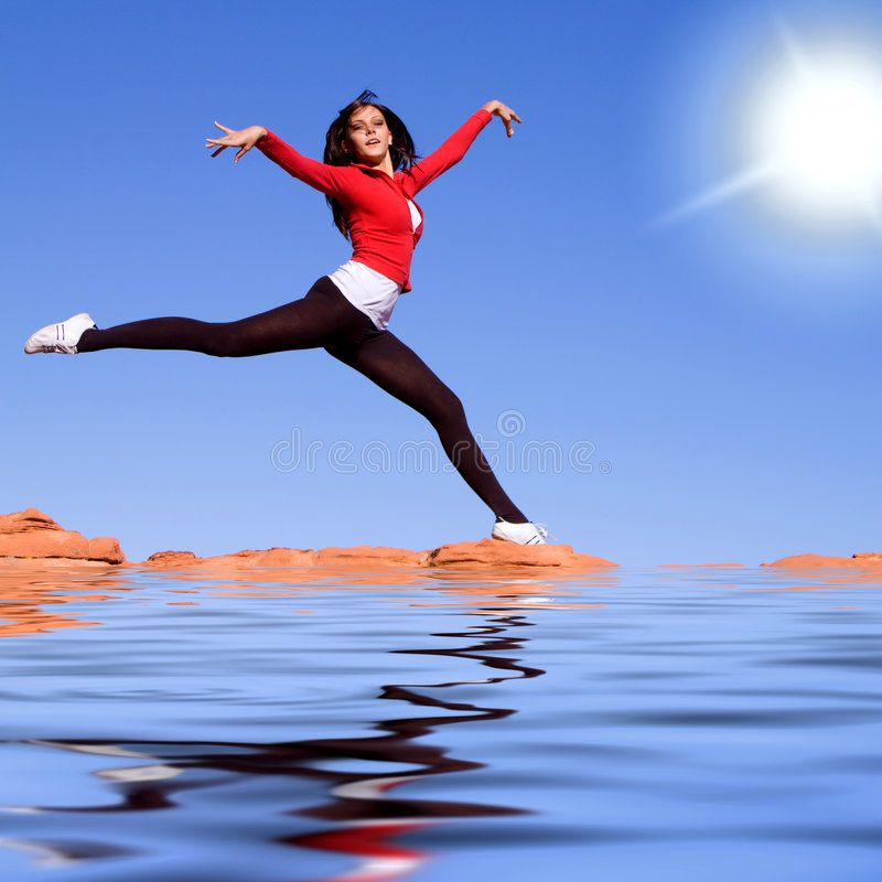 Young athletic woman jumping on the water. Beautiful young athletic woman jumping high stock image