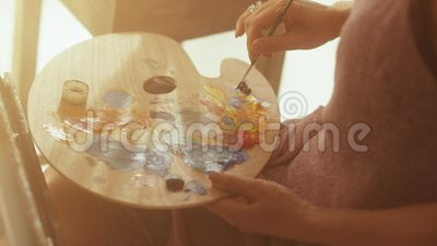 Middle aged woman artist is painting on canvas sitting in daylight art studio stock video footage