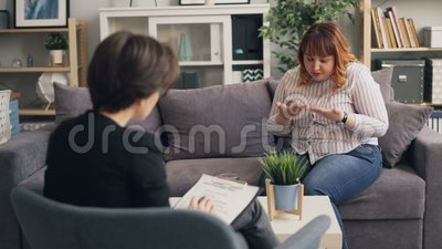 Overweight young lady opening up to experienced psychologist during consultation stock footage